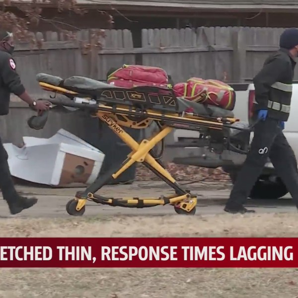 Two EMTs carry stretcher into home