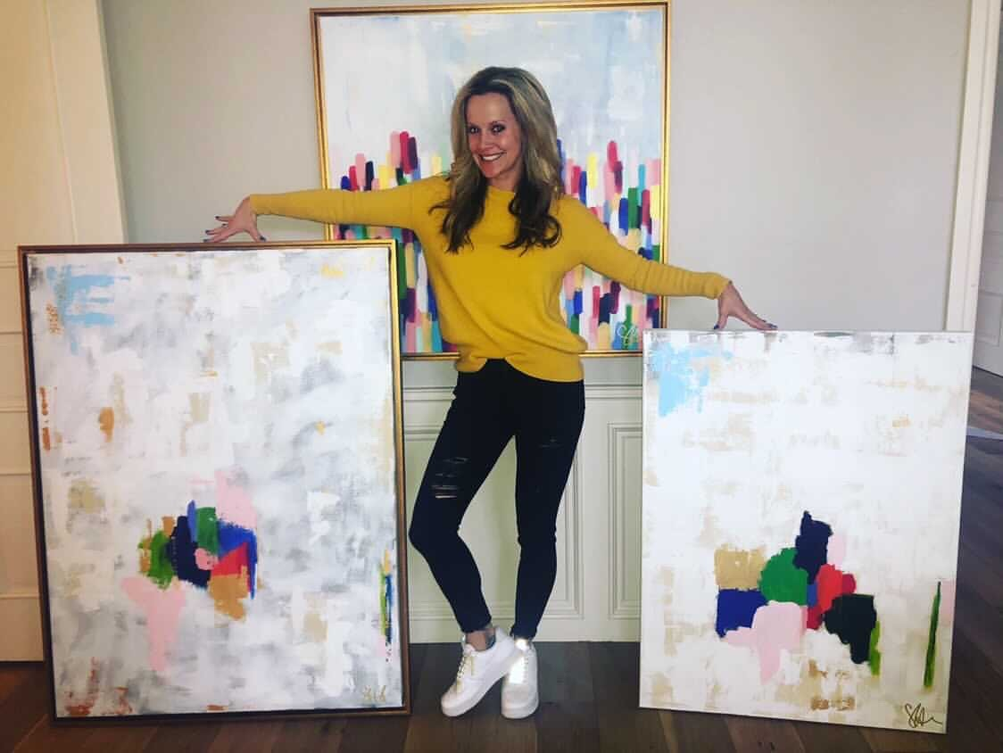 Visual artist, Stacey Haggard, posing with two of her past abstract canvas pieces. Haggard is one of 30 participating artists and has entered two canvases for the Saturday, August 7, 2021 Resilience Art Show and Auction for Calm Waters.