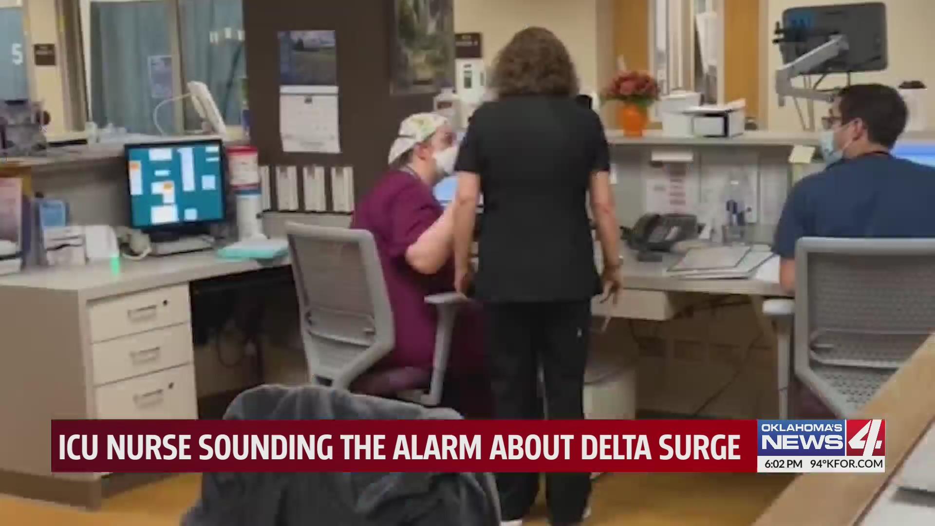 Three nurses talk amongst themselves at nurses' station