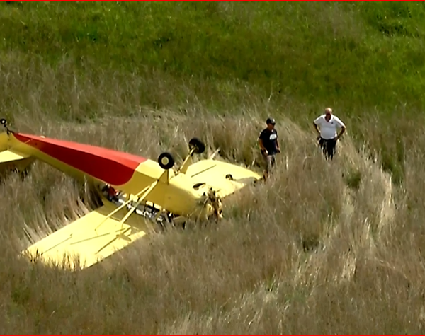 image of plane upside down in field