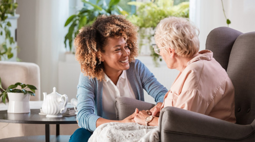Home health care worker talks with elderly patient
