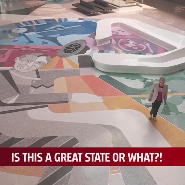 Artist Matt Goad walks along his art piece in the Will Rogers Airport terminal