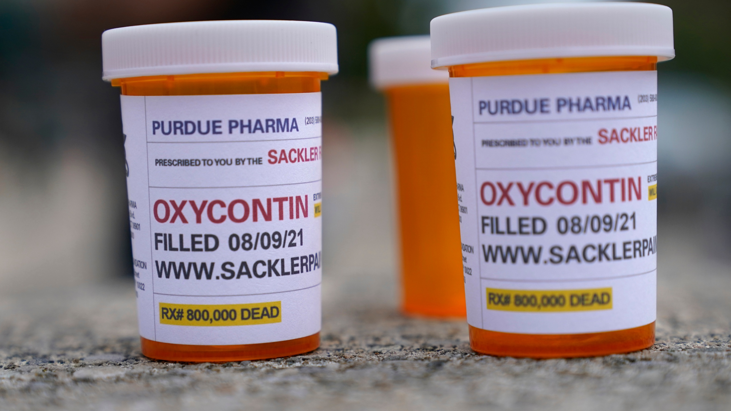 Fake pill bottles with messages about Purdue Pharma are displayed during a protest outside the courthouse where the bankruptcy of the company is taking place in White Plains, N.Y.
