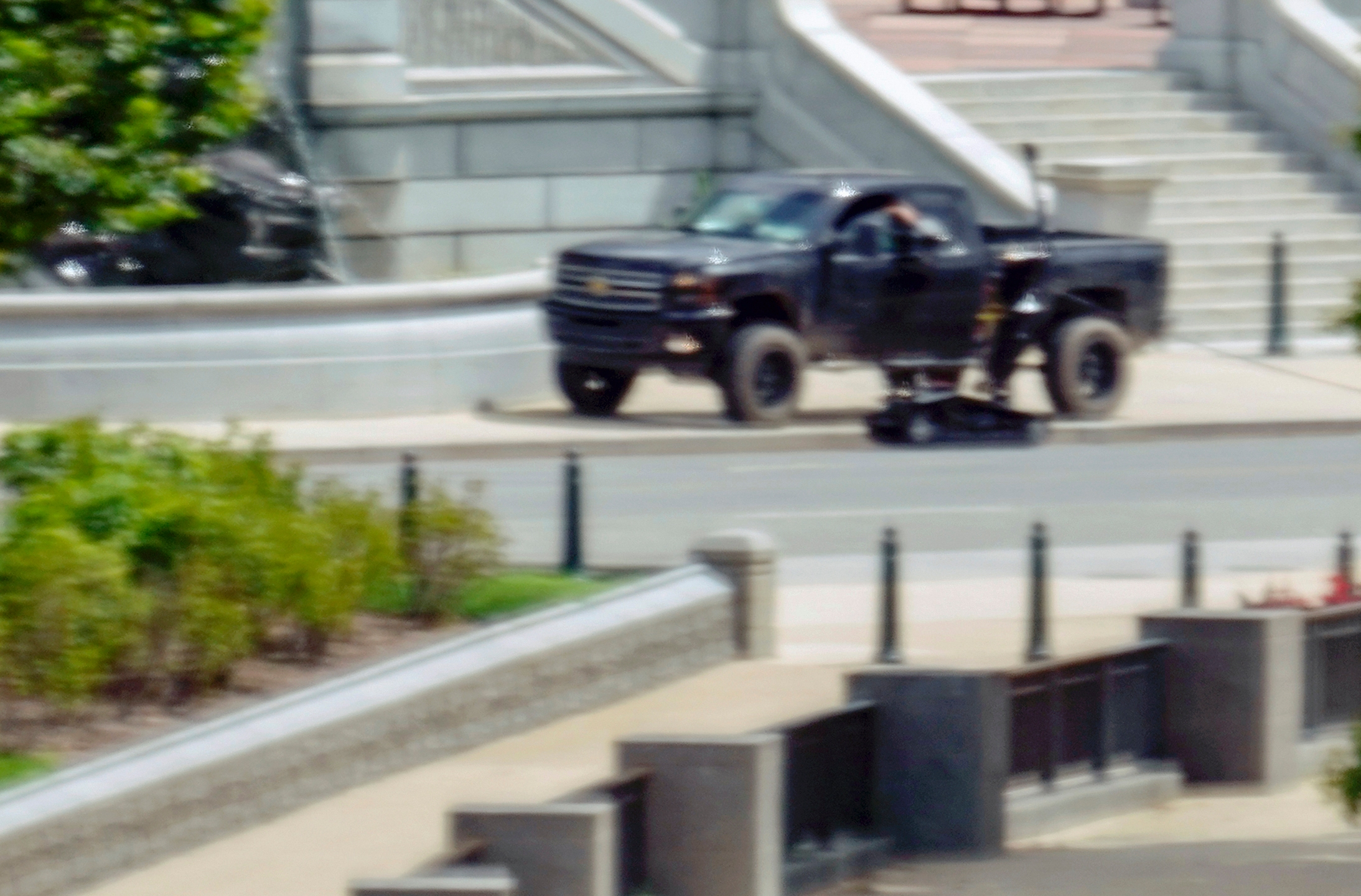 A robot is seen near a person in a pickup truck parked on the sidewalk in front of the Library of Congress' Thomas Jefferson Building, as seen from a window of the U.S. Capitol, Thursday, Aug. 19, 2021, in Washington. A man sitting in the pickup truck outside the Library of Congress has told police that he has a bomb, and that's led to a massive law enforcement response to determine whether it's an operable explosive device. (AP Photo/Alex Brandon)