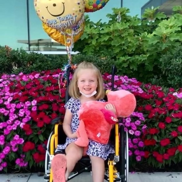 Aurora poses outside Children's before heading home from her COVID-19 stay