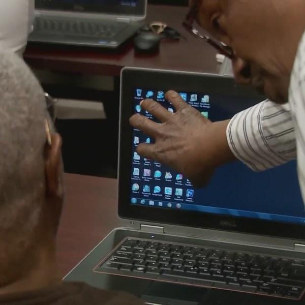 Instructor teaches elderly man on computer