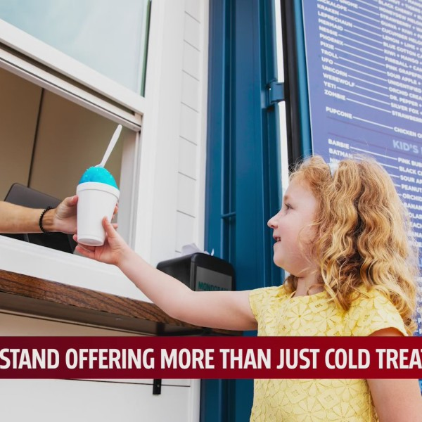 Teen working Sasquatch Shaved Ice stand hands young girl a blue snowcone