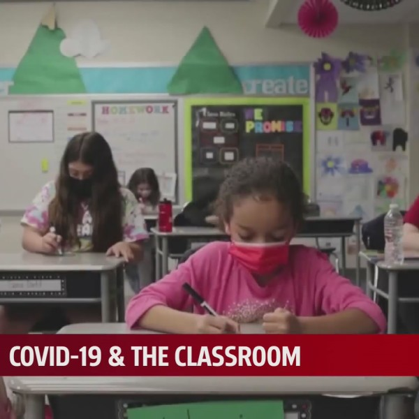 Students in masks write at desks in classroom