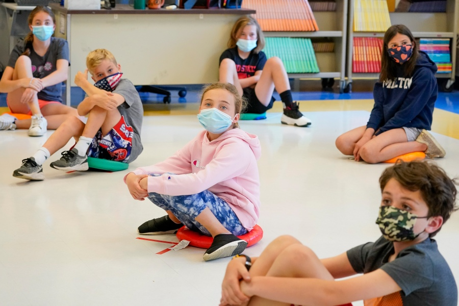 FILE - In this May 18, 2021 file photo, fifth-graders wearing face masks are seated at proper social distancing during a music class at the Milton Elementary School in Rye, N.Y. (AP Photo/Mary Altaffer, File)