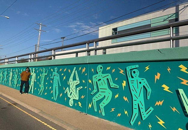 """Joe Slack with his piece, Birdwatching OKC Lightning Thunder Dance Party"""", which can be found along Classen Boulevard, between 7th and 9th Street"""