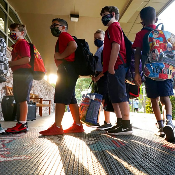 In this Aug. 17, 2021, file photo, wearing masks to prevent the spread of COVID-19, elementary school students line up to enter school for the first day of classes in Richardson, Texas