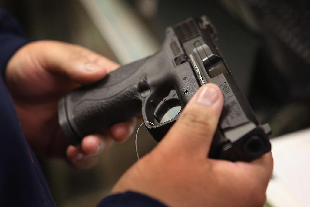 A customer shops for a pistol at Freddie Bear Sports sporting goods store on December 17, 2012 in Tinley Park, Illinois. (Photo by Scott Olson/Getty Images)