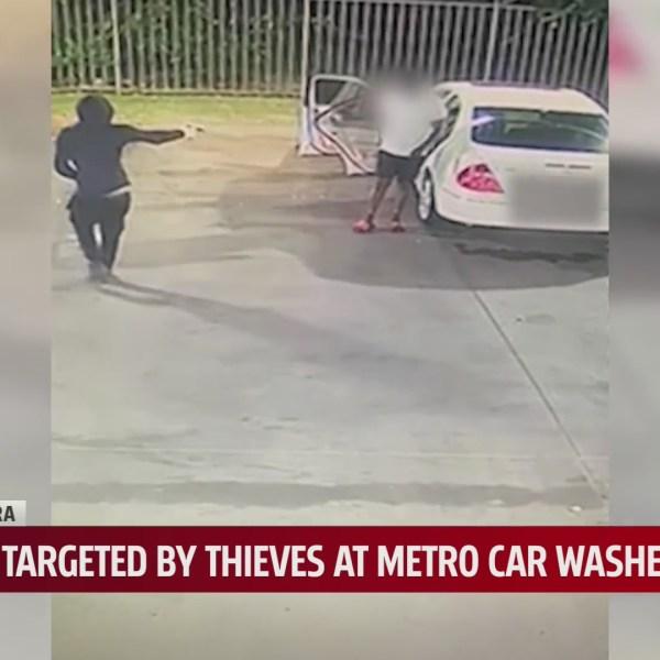 Surveillance video shoes suspect pointing gun at man vacuuming out his car at The Car Wash
