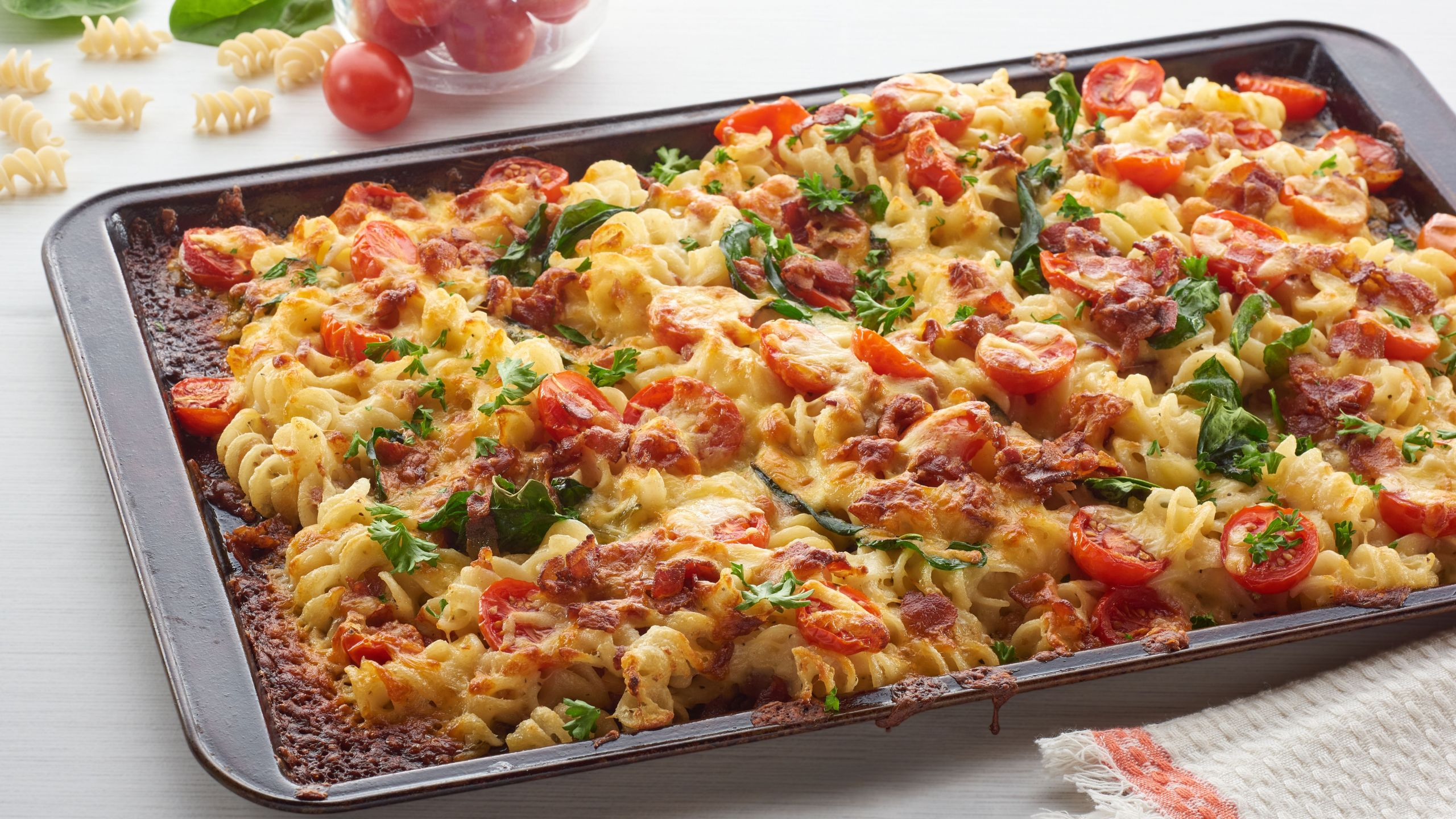 Sheet pan pasta with spinach, tomato, and bacon