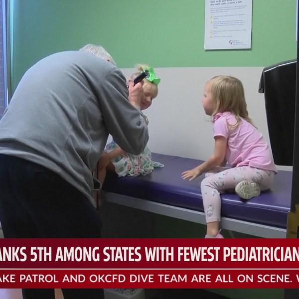 Pediatrician examines two patients